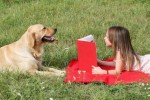 Girl and dog reading book